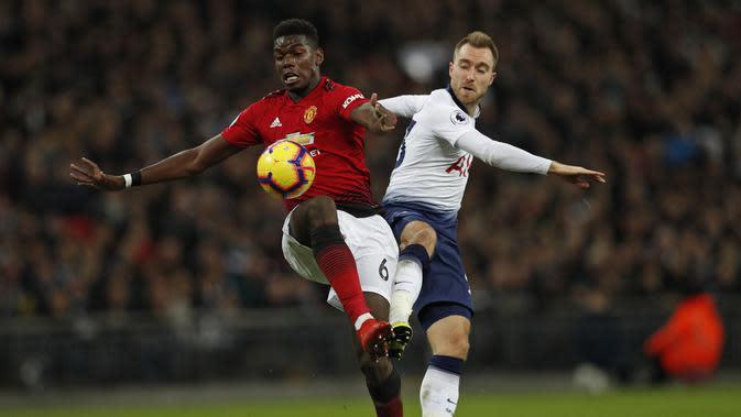Paul Pogba berduel dengan Christian Eriksen pada laga lanjutan Premier League yang berlangsung di stadion Wembley, Inggris, Minggu (13/1). Man United menang atas Tottenham Hotspur 1-0. (AFP/Adrian Dennis)