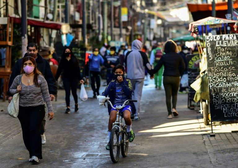 People walk in a commercial street in Villa 31