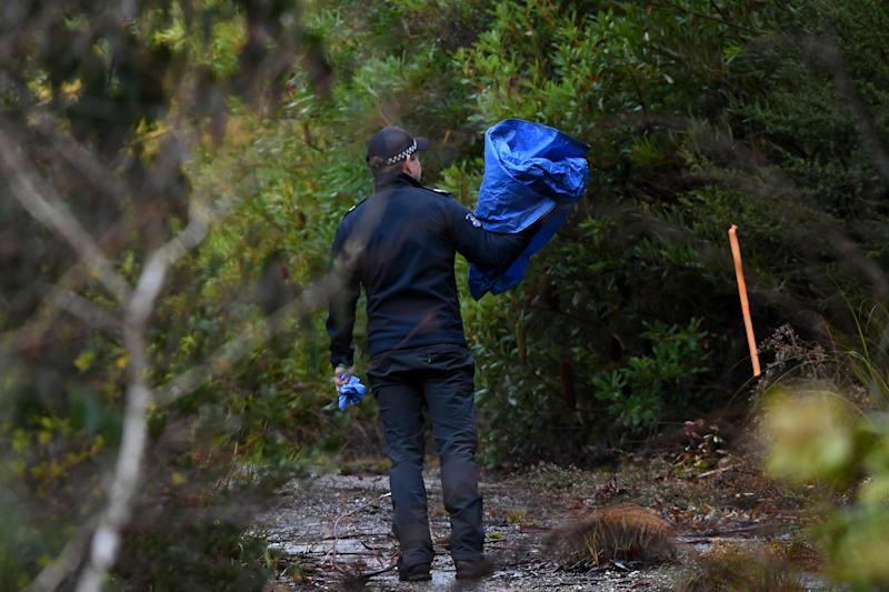 A Police officer carries a blue tarp in Marysville, Victoria, Monday, July 15, 2019. The search continues for Poshik Sharma, who has been missing after an argument with friends in Marysville.