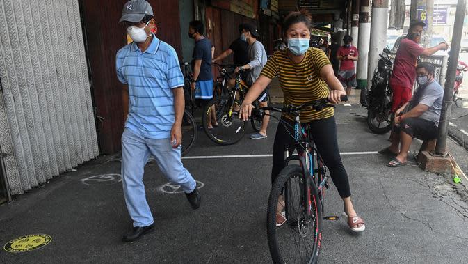 Seorang pekerja rumah sakit pemerintah mengendarai sepedanya yang baru dibeli di Manila pada 20 Mei 2020. Alat transportasi umum yang masih beroperasi dalam kapasitas terbatas membuat warga Filipina beralih ke sepeda saat berakhirnya masa karantina dan dimulainya periode New Normal. (Ted ALJIBE/AFP)
