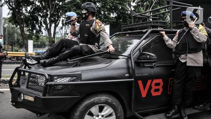 Aparat kepolisian menggunakan toa saat mengusir massa buruh yang akan berunjuk rasa di sekitar Gedung DPR RI, Jakarta, Kamis (8/10/2020). Polri mengerahkan 2.500 personel BKO Brimob Nusantara untuk mengamankan unjuk rasa UU Cipta Kerja di Gedung DPR dan sekitarnya. (merdeka.com/Iqbal S. Nugroho)