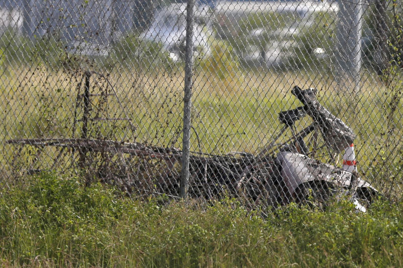 The charred wreckage of a private plane is seen in a field near the Industrial Canal and New Orleans Lakefront airport.