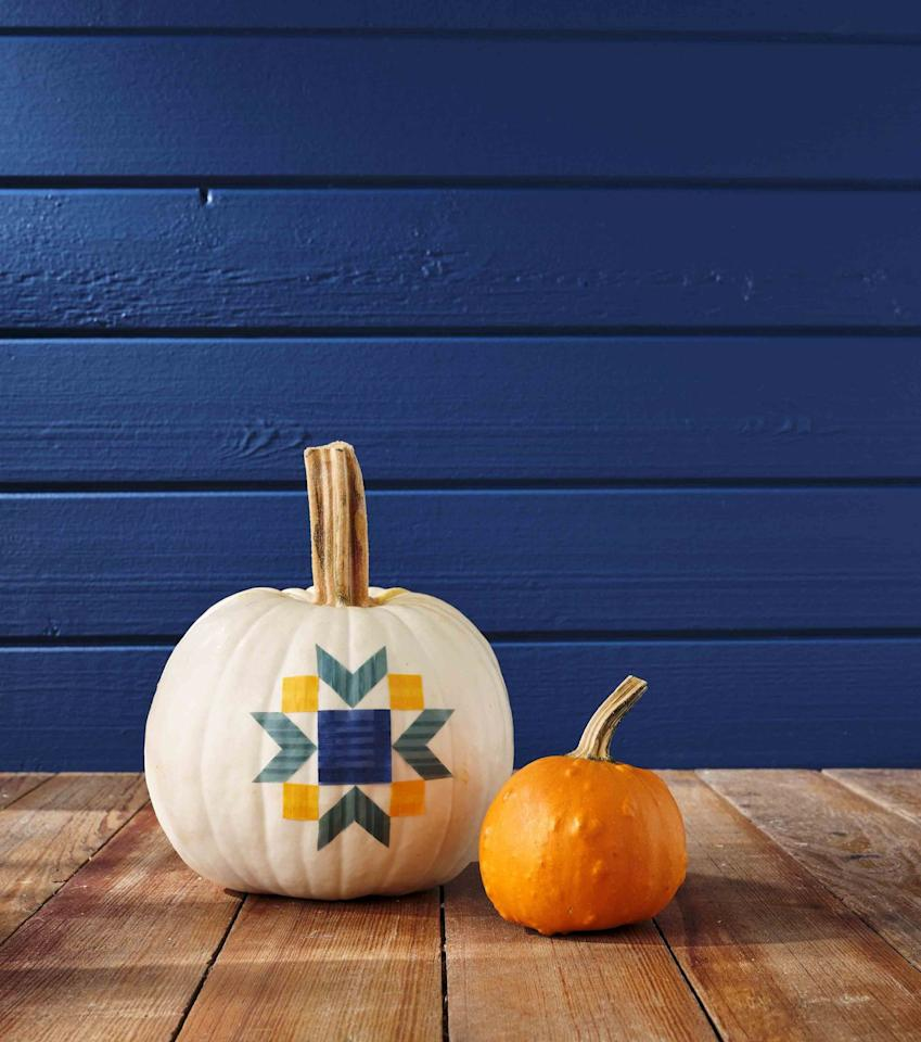 """<p>What's more country than a warm and cuddly quilt—even if it's made with tape!<strong><br></strong></p><p><strong>Make the pumpkin:</strong> Draw a quilt pattern on a piece of scratch paper. Cut lengths of washi tape to fit pattern, attaching them to a medium-size white pumpkin as you go.</p><p><a class=""""body-btn-link"""" href=""""https://www.amazon.com/Rolls-Decorative-Masking-Crafts-Wrapping/dp/B06XNJH7YK/ref=sr_1_19?tag=syn-yahoo-20&ascsubtag=%5Bartid%7C10050.g.1350%5Bsrc%7Cyahoo-us"""" target=""""_blank"""">SHOP WASHI TAPE</a></p>"""