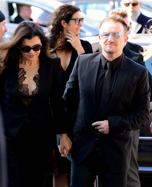 U2 singer Bono, right arrives with his wife Ali Hewson for the funeral of Irish poet Seamus Heaney, at the Church of the Sacred Heart in Donnybrook, Dublin, Ireland, Monday, Sept. 2, 2013. Ireland mourned the loss of its Nobel laureate poet, Seamus Heaney, with equal measures of poetry and pain Monday in a funeral full of grace notes and a final message from the great man himself: Don't be afraid. Among those packing the pews of Dublin's Catholic Church of the Sacred Heart were government leaders from both parts of Ireland, poets and novelists, Bono and The Edge from rock band U2, and former Lebanese hostage Brian Keenan. Heaney won the Nobel Prize for literature in 1995 in recognition of his wide-ranging writings inspired by the rural wonders of Ireland, the strife of his native Northern Ireland, the ancient cultures of Europe, of Catholic faith and Celtic mysticism, and the immutability of family ties. He died Friday in a Dublin hospital at the age of 74. (AP Photo/Peter Morrison)