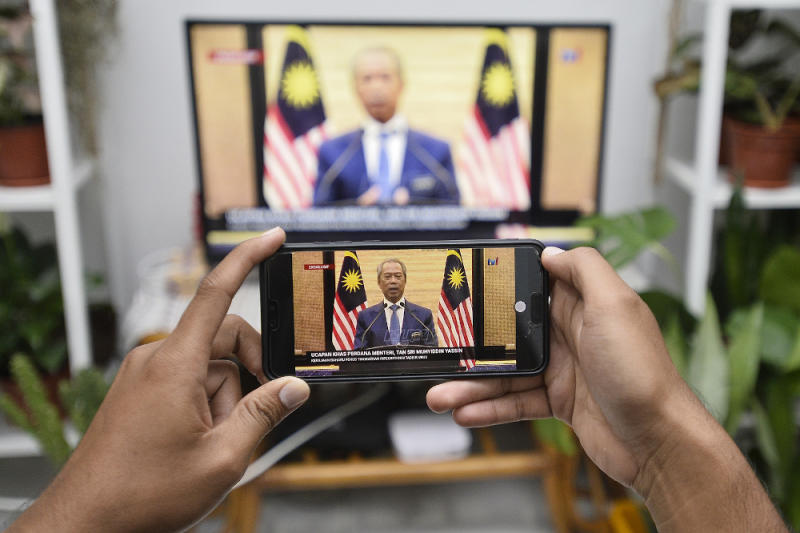 A man watches a live telecast of Prime Minister Tan Sri Muhyiddin Yassin in Shah Alam on March 2, 2020. — Picture by Miera Zulyana
