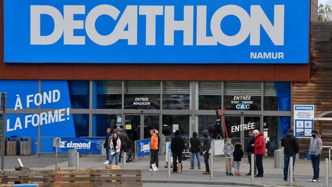 Orang-orang menjaga jarak aman ketika antre di luar toko olahraga Decathlon setelah pelonggaran lockdown secara bertahap di Namur, Senin (11/5/2020). Warga Belgia rela mengantre selama beberapa jam sebelum toko dibuka untuk berbelanja pertama kalinya sejak lockdown pada Maret lalu. (JOHN THYS/AFP)