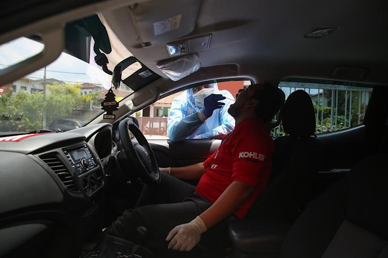 A health worker in protective suit tests a man for Covid-19 at a drive-through testing site at KPJ Damansara Specialist Hospital in Petaling Jaya March 28, 2020. — Picture by Yusof Mat Isa