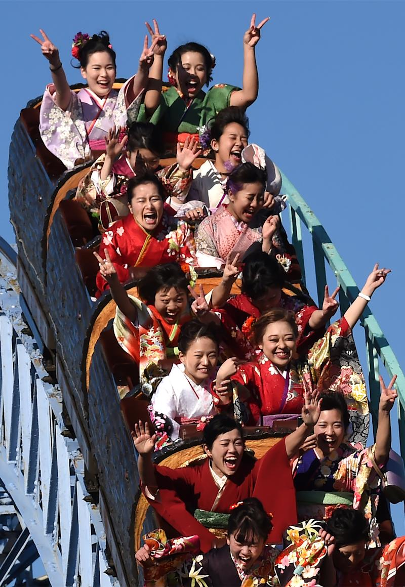 """Twenty-year-old Japanese women dressed in kimonos take a ride on a roller-coaster after their """"Coming-of-Age Day"""" celebration ceremony at Toshimaen amusement park in Tokyo on January 14, 2019. (Photo by Kazuhiro NOGI / AFP) (Photo credit should read KAZUHIRO NOGI/AFP via Getty Images)"""
