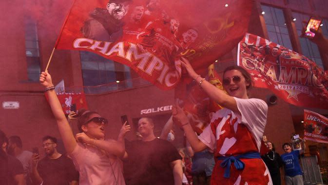 Para fans merayakan Liverpool memenangkan gelar juara Liga Primer Inggris setelah kemenangan Chelsea 2-1 atas Manchester City, di luar stadion Anfield di Liverpoo (25/6/2020). Pasukan Jurgen Klopp memastikan gelar liga ke-19 untuk klub dengan rekor tujuh pertandingan tersisa. (AFP Photo/Oli Scarff)