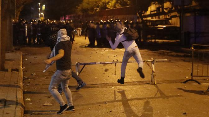 Demonstran antipemerintah bentrok dengan polisi antihuru-hara saat protes menentang elite penguasa di Beirut, Lebanon, Selasa (14/1/2020). Demonstran menganggap elite penguasa gagal mengatasi ekonomi yang menurun tajam. (AP Photo/Hussein Malla)