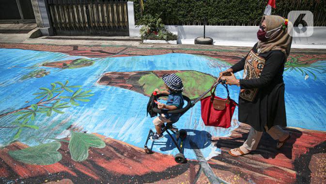 Warga melintas di atas jalan yang telah dilukis mural di Jalan Keuangan, Cilandak, Jakarta, Rabu (26/8/2020). Mural di sepanjang jalan Keuangan menuju museum Basoeki Abdullah itu bertujuan memperindah wilayah tersebut serta sebagai ajang promosi museum. (Liputan6.com/Faizal Fanani)