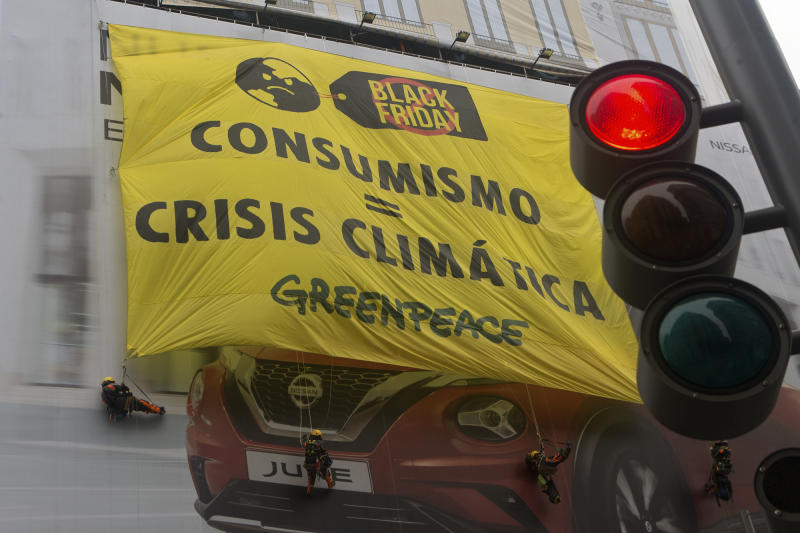 Greenpeace activists hang from a giant banner covering a car advert reading 'Consumo equals Climatic Crisis' during a Black Friday sale in Madrid, Spain, Friday, Nov. 29, 2019. (AP Photo/Paul White)