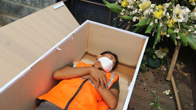 PETI MATI PELANGGAR PSBB: Warga pelanggar PSSB dihukum masuk ke dalam peti mati di Kawasan Kalisari, Pasar Rebo, Jakarta Timur, Kamis (3/9/2020). Warga Kelurahan Pasar Rebo yang tak mengenakan masker diberi pilihan hukuman, salah satunya dimasukkan ke dalam peti mati. (Liputan6.com.Herman Zakharia)