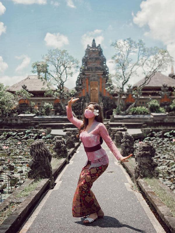Pertama, ada Jessica Mila yang belum lama ini berlibur ke Pulau Dewata Bali dan tampil seperti perempuan di sana. Kebaya pink dipadukan kain khas Bali yang warnanya senada dengan pita di pinggangnya. Bunga di telinga membuatnya makin cantik. (Instagram/jscmila)