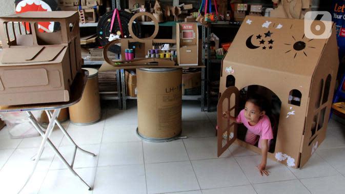 Seorang anak bermain dalam rumah-rumahan dari kardus di Rumah Mainan Kardus, Depok, Jawa Barat, Kamis (1/10/2020). Mainan berbahan baku kardus tersebut dijual dengan harga Ro 50 ribu hingga Rp 1.200.000 tergantung besar kecil ukuranya dan tingkat kesulitan. (merdeka.com/Arie Basuki)