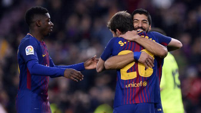Penyerang Barcelona, Luis Suarez (kanan) mendapat ucapan selamat dari Sergi Roberto dan Ousmane Dembele (kiri) usai mencetak gol ke gawang Levante, pada laga lanjutan La Liga 2017-2018, di Estadio Camp Nou, Minggu (7/1/2018) malam WIB. (AFP/Josep Lago)