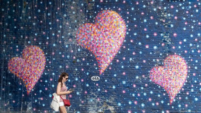Seorang perempuan melewati lukisan mural lambang cinta di London, Inggris, pada 1 Agustus 2020. Pemerintah Inggris pada Jumat (31/7) mengumumkan penundaan pelonggaran beberapa langkah pembatasan menyusul jumlah infeksi virus corona yang meningkat. (Xinhua/Han Yan)