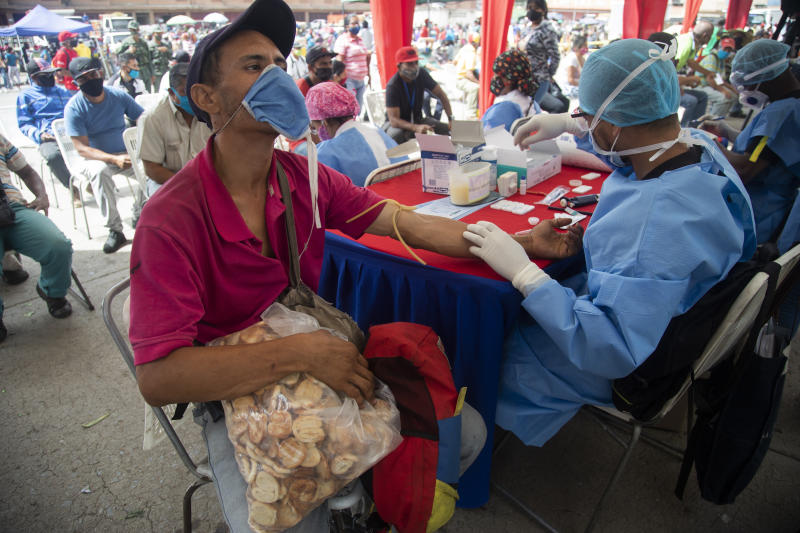 A health worker takes a blood sample for a quick COVID-19 test from man who works selling cookies at the Coche food market in Caracas, Venezuela, Tuesday, June 23, 2020. Health authorities tested people arriving at the market as a preventive measure to help curb the spread of the new coronavirus. (AP Photo/Ariana Cubillos)
