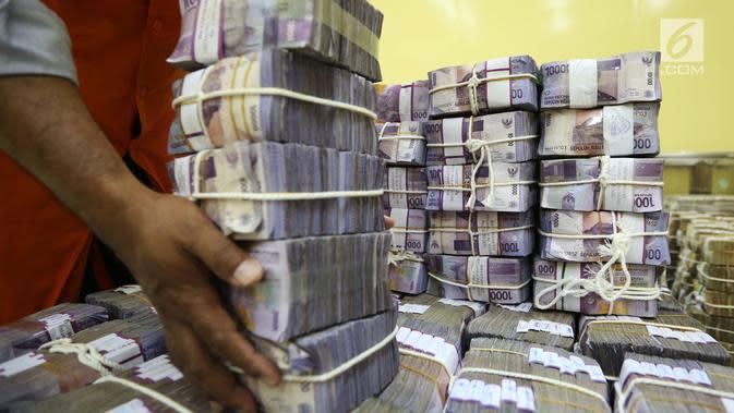 Petugas menata tumpukan uang kertas di ruang penyimpanan uang