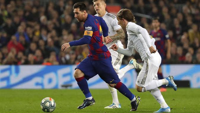 Penyerang Barcelona, Lionel Messi menggiring bola dari kejaran gelandang Real Madrid, Luka Modric pada pertandingan lanjutan La Liga Spanyol di stadion Camp Nou (18/12/2019). Barcelona bermain imbang 0-0 atas Real Madrid. (AP Photo/Emilio Morenatti)