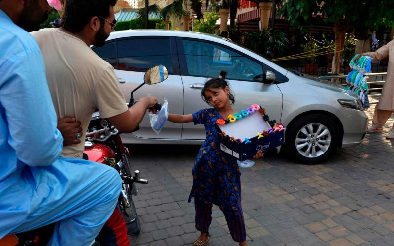 A girl sells a facemask to costumers at Pindi Food Street in Rawalpindi - FAROOQ NAEEM/AFP