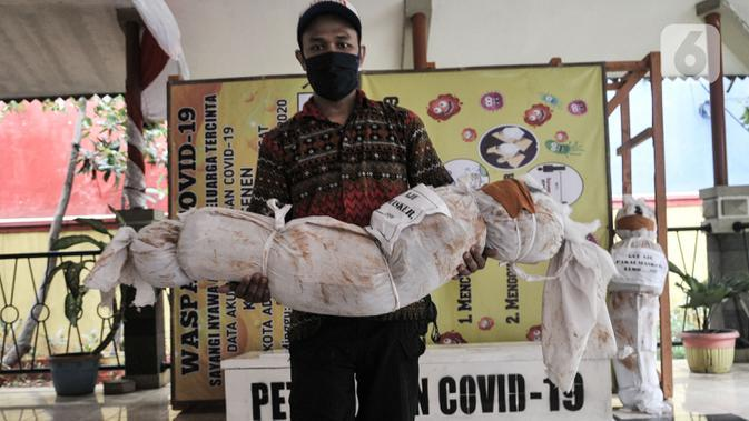 Pekerja mengendong boneka pocong untuk dipajang di Kantor Kecamatan Senen, Jakarta, Kamis (13/8/2020). Pemkot Jakpus menyiapkan peti mati dan boneka pocong di setiap kecamatan sebagai peringatan akan bahaya Covid-19 dan imbauan untuk tidak mengabaikan protokol kesehatan. (merdeka.com/Iqbal Nugroho)