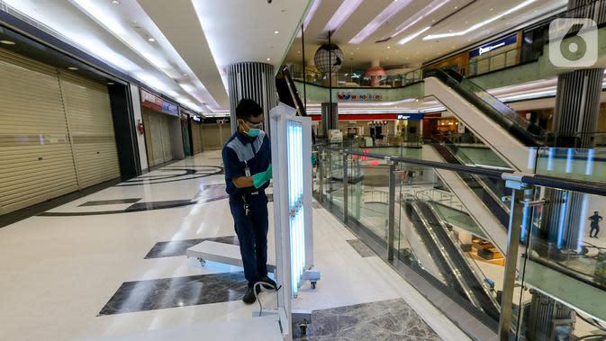 Petugas melakukan penyemprotan disinfektant dengan sinar UV di area kaca Lippo Mall Puri, Jakarta, Rabu (3/6/2020). Lippo Malls Indonesia (LMI) menyiapkan prosedur dengan menerapkan protokol kesehatan menuju new normal di seluruh mal di 34 kota besar di Indonesia. (Liputan6.com/Fery Pradolo)