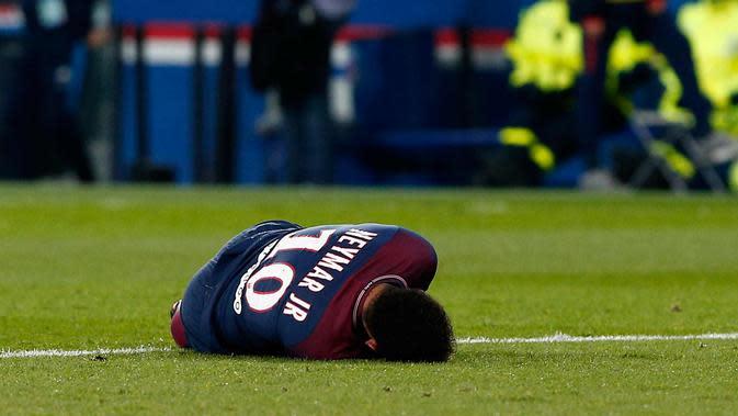 Penyerang PSG, Neymar Jr tergeletak di lapangan setelah mengalami cedera saat bertanding melawan Marseille di Liga Prancis di Stadion Parc des Princes, (25/2). Pergelangan kaki Neymar cedera setelah mendarat dengan tidak pas. (AP Photo/Thibault Camus)