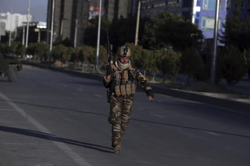 An Afghan security forces works at the site where a bus carrying local TV station employees hit a roadside bomb in Kabul, Afghanistan, Saturday, May 30, 2020. (AP Photo/Rahmat Gul)