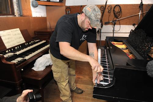 Billy Brasile, of JP's Piano Movers, Oxford, Michigan, installs a keyboard cover at Detroit's Motown Museum where the museum's prized Steinway grand piano was moved back into Studio A on Monday, April 1, 2013. The 1877 Steinway grand piano used by Motown greats during the label's 1960s heyday, and restored thanks to Paul McCartney, is back home in Detroit. (AP Photo/The Detroit News, Max Ortiz)
