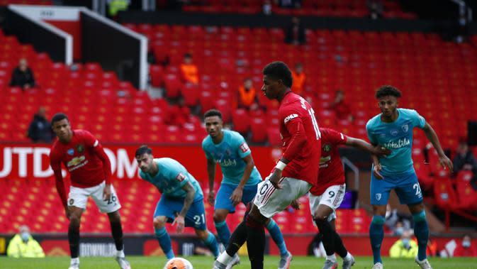 Penyerang Manchester United (MU), Marcus Rashford saat mengeksekusi penalti ke gawang Bournemouth di Old Trafford, Sabtu (4/7/2020). (Clive Brunskill/Pool via AP)