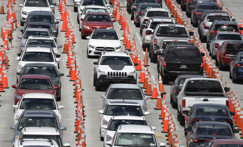 FILE - In this June 26, 2020, file photo lines of cars wait at a coronavirus testing site outside of Hard Rock Stadium in Miami Gardens, Fla. (AP Photo/Wilfredo Lee, File)