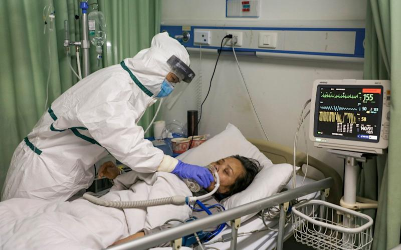 A nurse feeds water to a patient in the isolation ward for coronavirus patients at a hospital in Wuhan - CHINATOPIX/AP