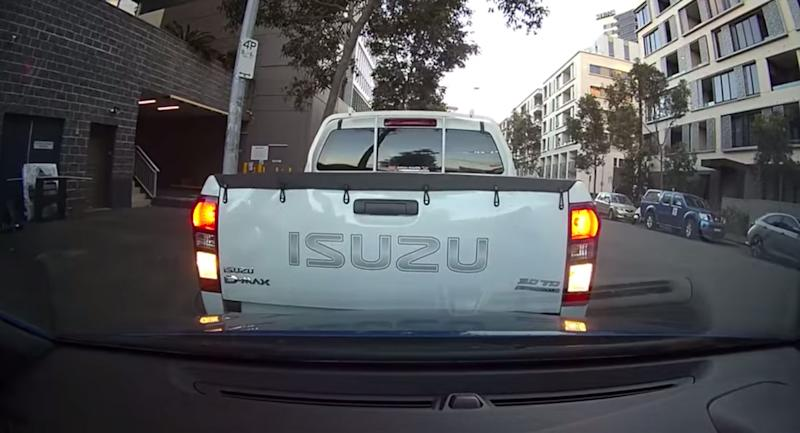 A ute driven by two City of Sydney parking inspectors backs into a car while parking.