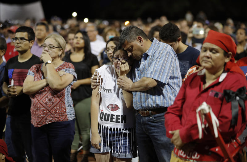 People comfort each other during a vigil for victims of Saturday's mass shooting at the shopping complex in El Paso. (AP)
