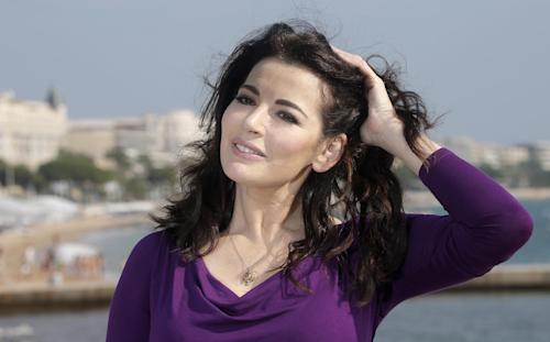 "FILE - In this Tuesday, Oct. 9, 2012 file photo, English food writer, journalist and broadcaster, Nigella Lawson poses during the 28th MIPCOM (International Film and Programme Market for TV, Video,Cable and Satellite) in Cannes, southeastern France. Celebrity chef Nigella Lawson and art collector Charles Saatchi say they intend to conclude a ""swift and amicable"" divorce by the end of the month, with neither receiving any financial compensation from the other. The couple separated after a newspaper published photos last month of Saatchi grasping his wife's throat during an argument at a London restaurant. A statement issued Monday, July 15, 2013, on their behalf said neither would contest the divorce ""and neither party will be making any financial claims against the other."" (AP Photo/Lionel Cironneau, File)"
