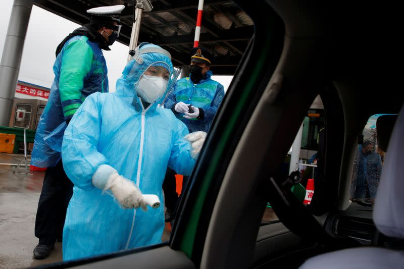 A medical worker checks a driver's temperature at a checkpoint as the country is hit by an outbreak of the novel coronavirus in Susong County