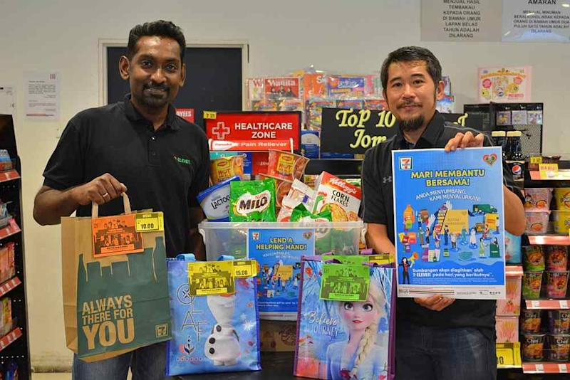 Ronan Lee (right) and General Manager of Operations Christopher Anthony making a contribution to Lend a Helping Hand Campaign 2020. — Picture courtesy of 7-Eleven Malaysia