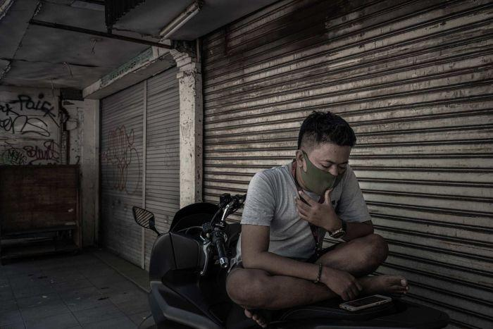 A man wears a mask while sitting on the back of his motorbike in front of closed shopfronts.