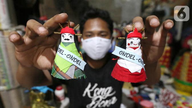 Pekerja menunjukkan ondel-ondel dari shuttlecock atau kok bekas di perkampungan Budaya Betawi, Srengseng Sawah, Jakarta, Sabtu (8/8/2020). Menyambut HUT Kemerdekaan RI produksi ondel-ondel dengan harga Rp 5 ribu per buahnya mulai banyak diburu. (Liputan6.com/Fery Pradolo)