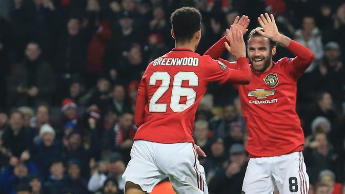 Pemain Manchester United, Juan Mata, merayakan gol yang dicetak Mason Greenwood ke gawang AZ Alkmaar pada laga Liga Europa di Stadion Old Trafford, Manchester, Rabu (12/12). MU menang 4-0 atas AZ. (AFP/Lindsey Parnaby)
