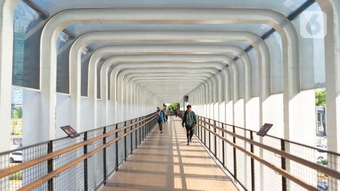 Pejalan kaki melintas di Jembatan Penyeberangan Orang (JPO) Bundaran Senayan, Jakarta, Jumat (15/11/2019). Untuk mencegah pengguna skuter listrik bermain di JPO, Dinas Bina Marga DKI menambahkan rambu larang melintas. (Liputan6.com/Immanuel Antonius)