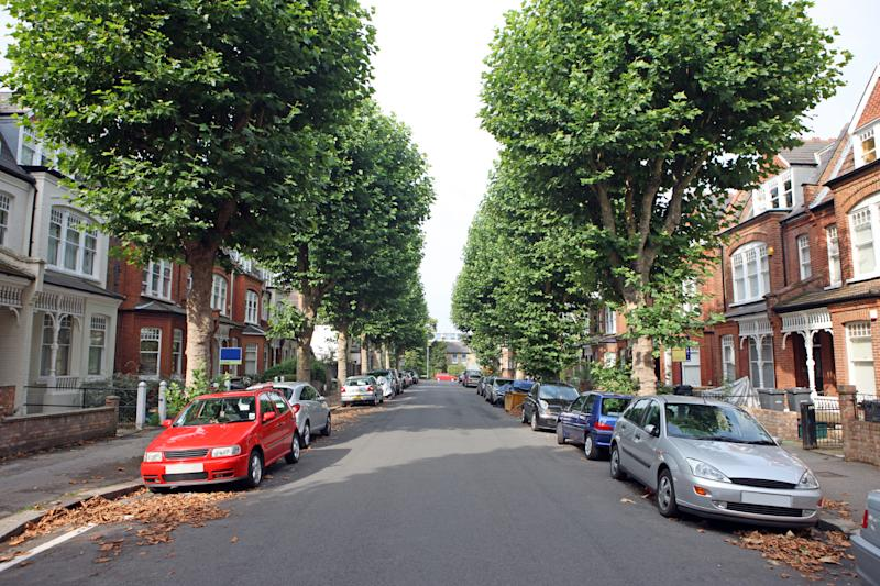 Tree lined UK street with cars parked on either side.
