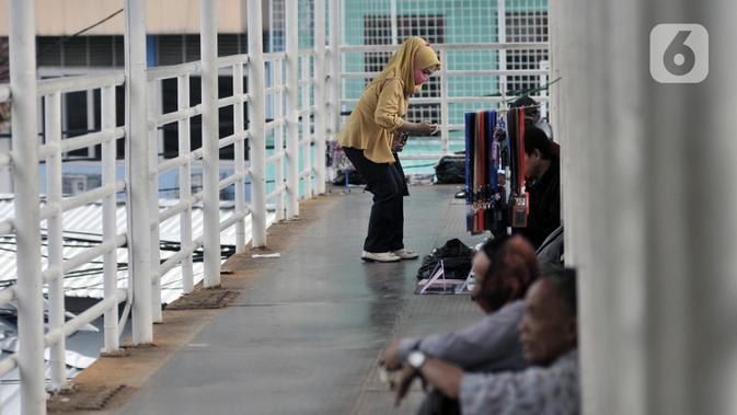 Warga mengenakan masker saat beraktivitas di kawasan Jatinegara, Jakarta, Selasa (12/5/2020). Berdasarkan Pergub Nomor 41 Tahun 2020, Pemprov DKI akan memberi sanksi teguran, kerja sosial, hingga denda Rp 250 ribu bagi warga yang tidak memakai masker saat keluar rumah. (merdeka.com/Iqbal S. Nugroho)
