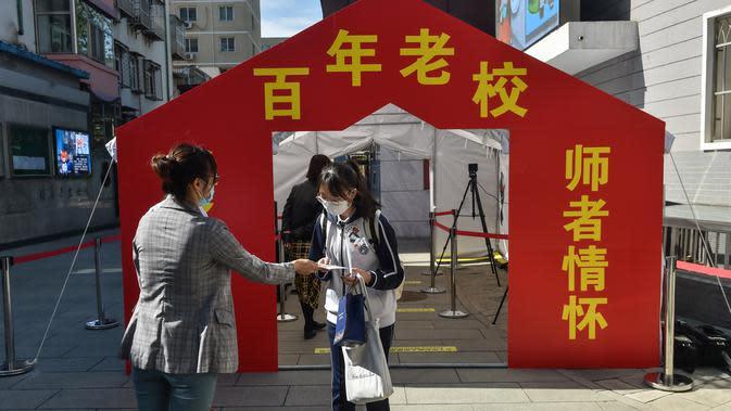 Seorang guru menyerahkan brosur tentang langkah pencegahan dan pengendalian wabah COVID-19 kepada seorang siswa yang hendak memasuki gedung Sekolah Menengah No. 166 di Beijing, ibu kota China, (11/5/2020). (Xinhua/Peng Ziyang)