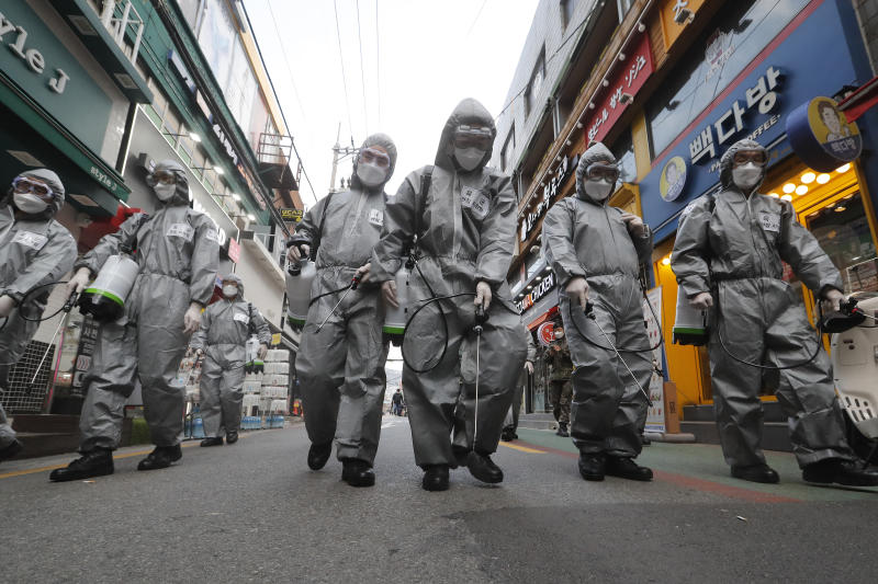 South Korean army soldiers wearing protective gears spray disinfectant as a precaution against the new coronavirus at a shopping street in Seoul, South Korea, Wednesday, March 4, 2020. The coronavirus epidemic shifted increasingly westward toward the Middle East, Europe and the United States on Tuesday, with governments taking emergency steps to ease shortages of masks and other supplies for front-line doctors and nurses. (AP Photo/Ahn Young-joon)