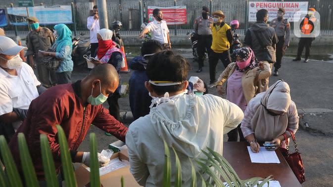 Petugas medis melakukan tes swab kepada pengguna KRL Commuter Line dengan metode polymerase chain reaction (PCR) di Stasiun Bekasi, Selasa, (5/5/2020). Pemkot Bekasi melakukan tes swab secara massal setelah tiga penumpang KRL dari Bogor terdeteksi terpapar virus corona (Liputan6.com/Herman Zakharia)
