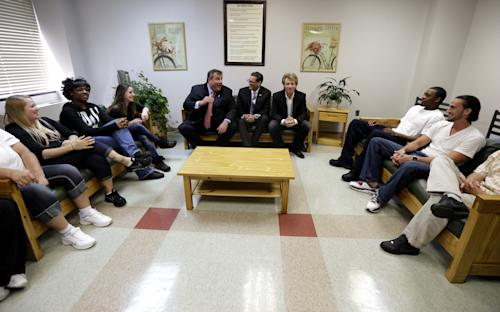 Dr. Manuel Guantez, center, sits with New Jersey Gov. Chris Christie, center left, and singer Jon Bon Jovi, center right, while visiting patients at the Turning Point drug rehab program at Barnert Medical Arts Complex, Thursday, May 2, 2013, in Paterson, N.J. During the visit, Christie signed into law a good Samaritan bill intended to assure that a fear of prosecution doesn't get in the way of medical help for overdose victims. The New Jersey law will shield from prosecution both overdose victims and those seeking medical help for them if they act in good faith. Bon Jovi's daughter suffered an apparent drug overdose on heroin in a dorm at Hamilton College in upstate New York last year. (AP Photo/Julio Cortez)