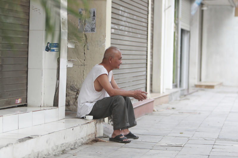 A man sits outside closed shops in Hanoi, Vietnam, Friday, March 27, 2020. Vietnam's Prime Minister Nguyen Xuan Phuc has ordered to shut down non-essential business to curb the spread of COVID-19. The new coronavirus causes mild or moderate symptoms for most people, but for some, especially older adults and people with existing health problems, it can cause more severe illness or death. (AP Photo/Hau Dinh)