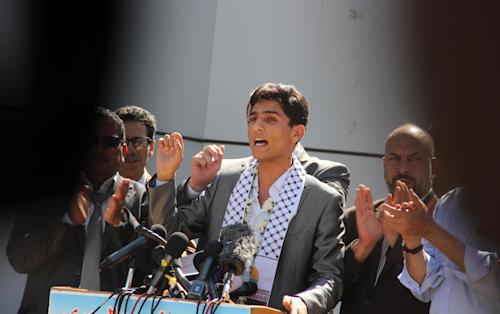 Arab Idol winner Palestinian Mohammed Assaf, speaks on arrival at the Rafah crossing point on the border between Egypt and southern Gaza Strip, Tuesday, June 25, 2013. Huge crowds of Gazans gave a gleeful welcome Tuesday to the first Palestinian winner of the Arab Idol talent contest, thronging the territory's border crossing with Egypt and the singer's home in hopes of embracing him, but internal politics surfaced quickly. Assaf's victory in the popular contest Saturday sparked huge celebrations in the West Bank and Gaza, giving Palestinians a sense of pride. (AP Photo/Khaled Omar, Pool)